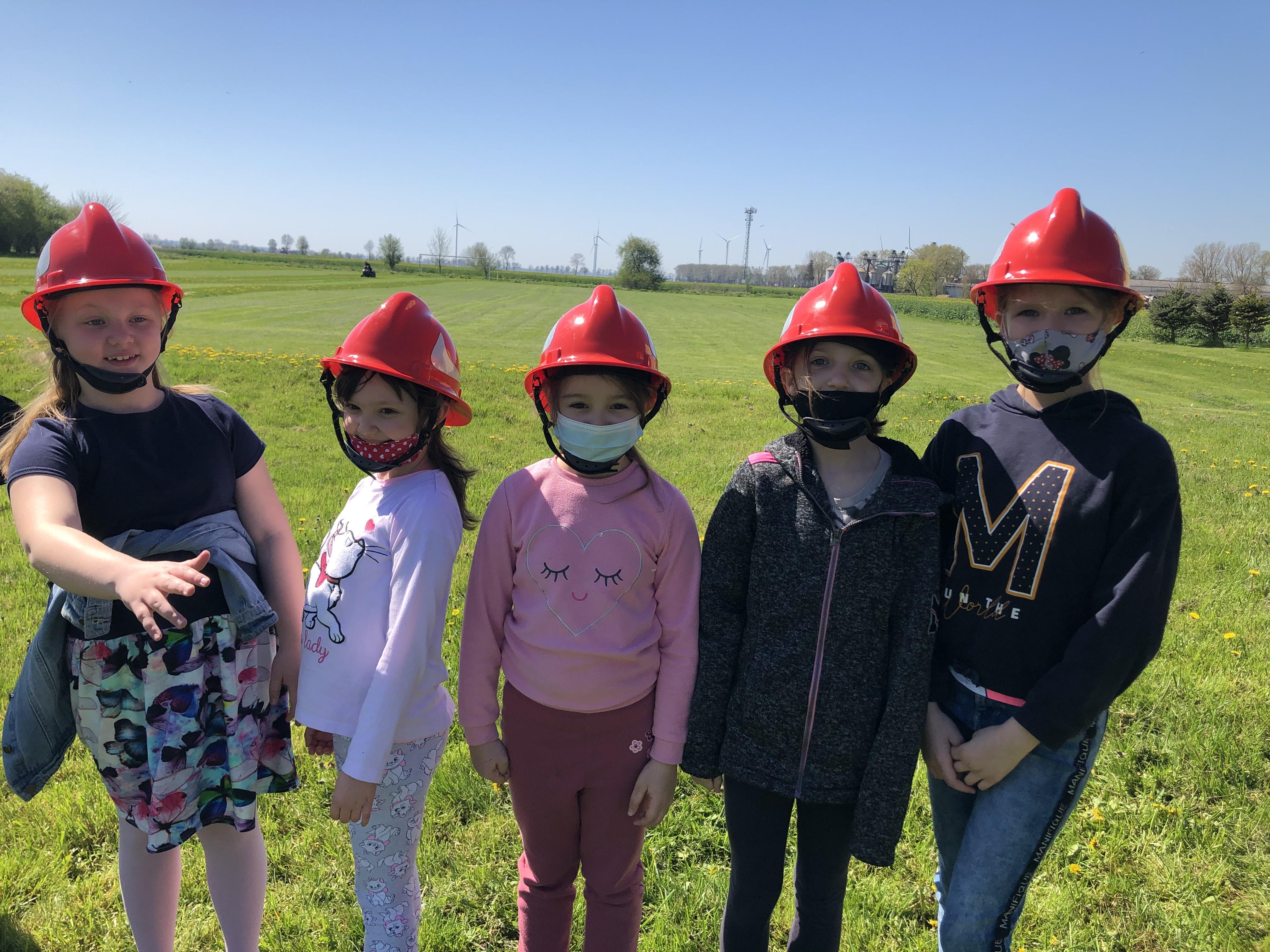 uczniowie z klasy pierwszej i trzeciej w kaskach strażackich