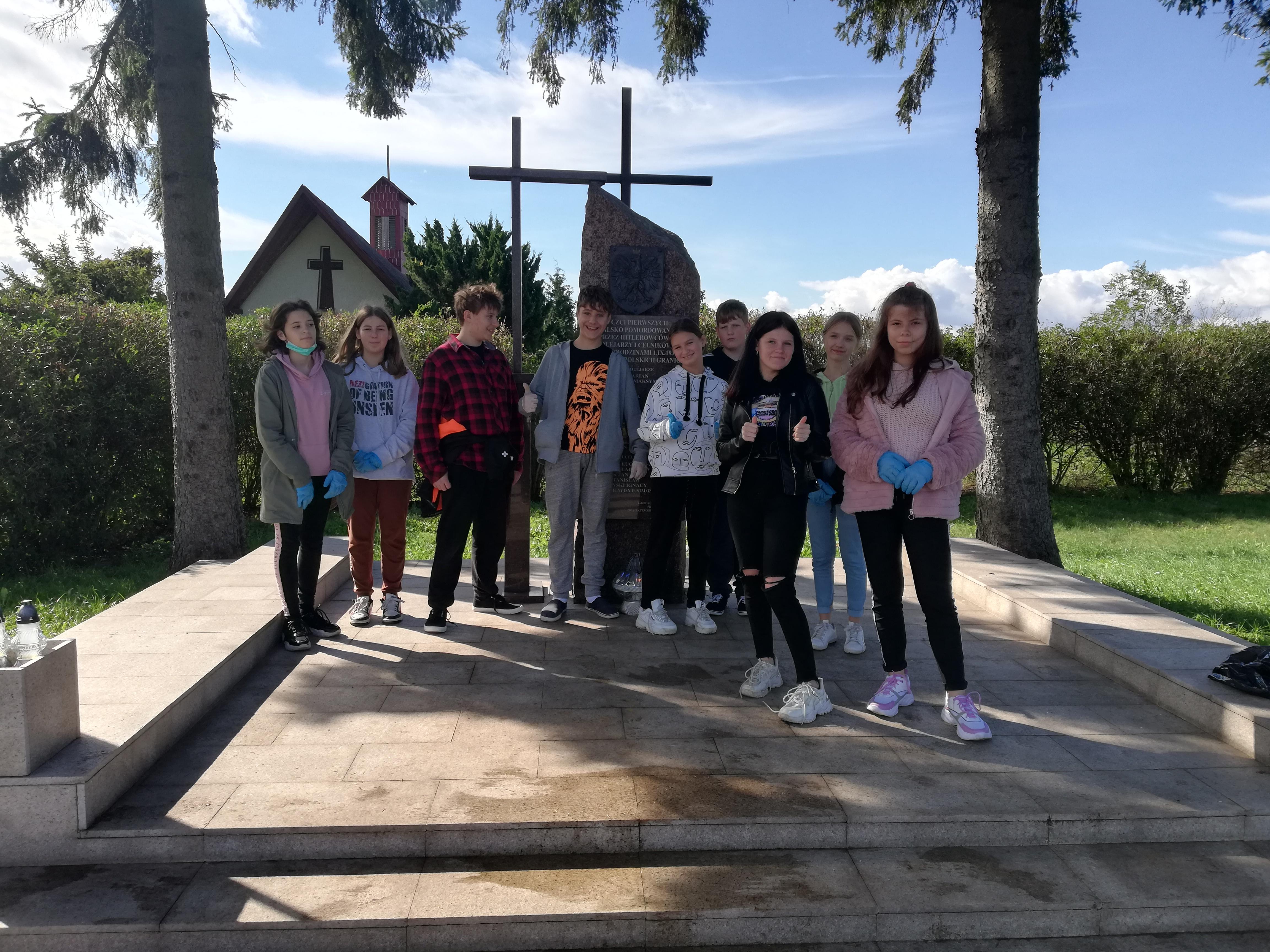 uczniowie kl. 8 przed posprzątanym pomnikiem